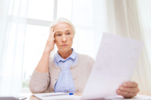 A stressed older woman with her hand to her head is looking at a piece of paper