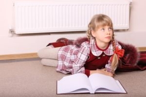 A blonde girl in a red dress with plaid accents and a book in front of her is sitting in front of a white cooling system