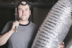 A Lubbock HVAC contractor holding ductwork and a tool in his left hand
