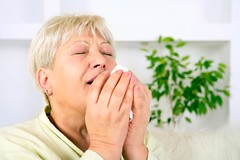 A blonde woman sneezing into a tissue
