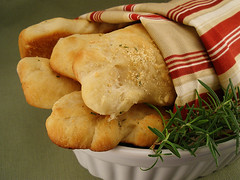 Parmesan rosemary breadsticks in a white bowl with a sprig of rosemary and a red, white, and beige cloth around them