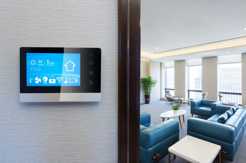 A smart thermostat on a gray wall